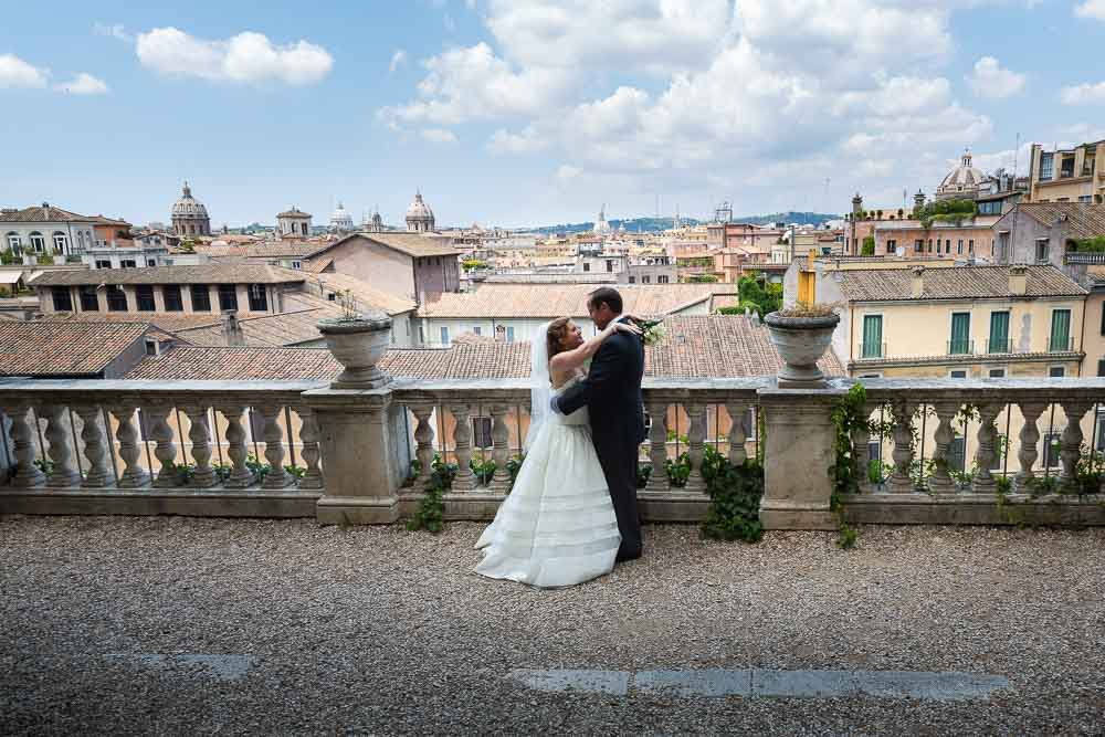 Just married in Rome. Groom and bride looking over the city of Rome from a panoramic view point