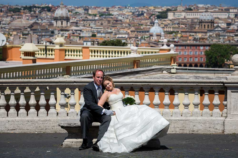Newlywed couple sitting down on a marble bench before the roman rooftops