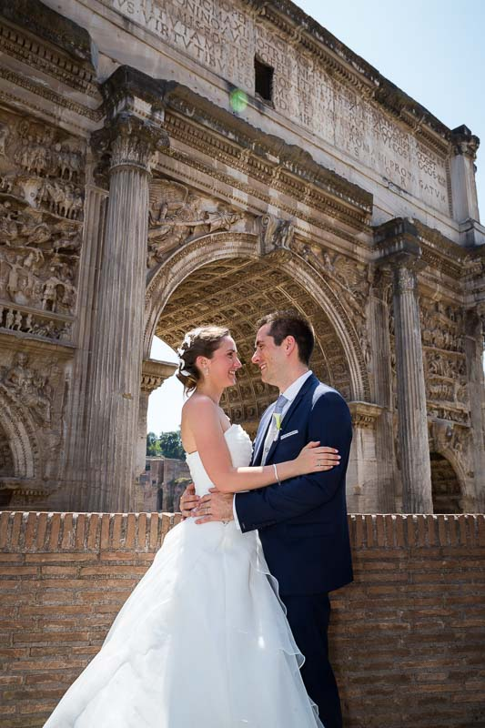 Just married couple photographed by a roman arch