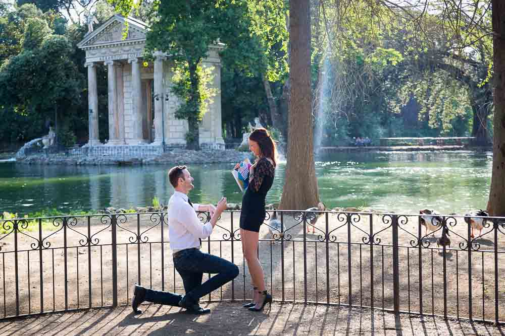 Man asking the big question. Proposing in Rome at the small lake of Villa Borghese in Rome Italy
