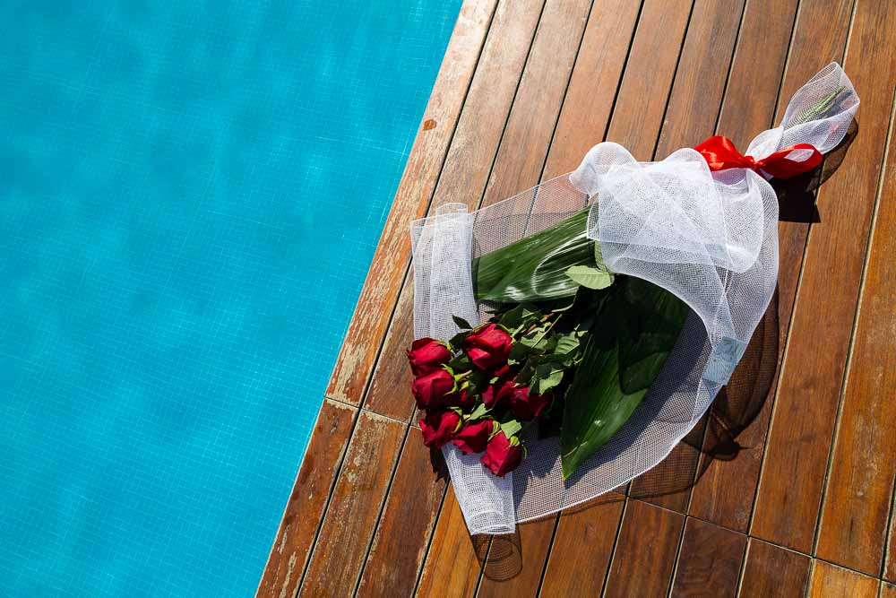 Bright red roses paying on the ground in between pools