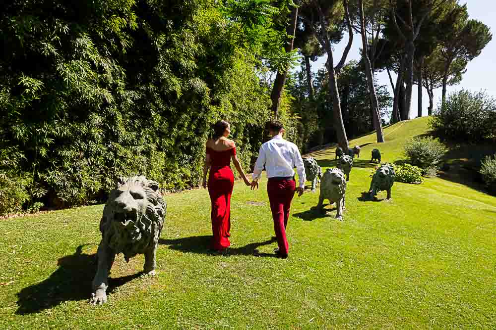 Couple walking hand in hand up a grass hill with lion statues