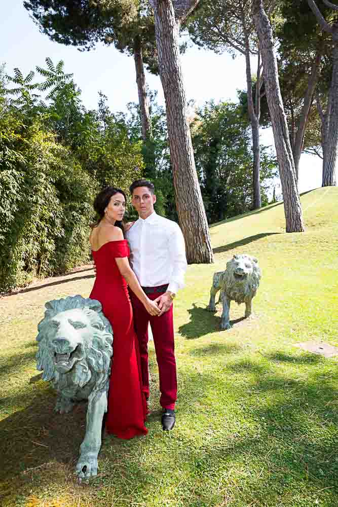 Posing by the lion statues in a grass field