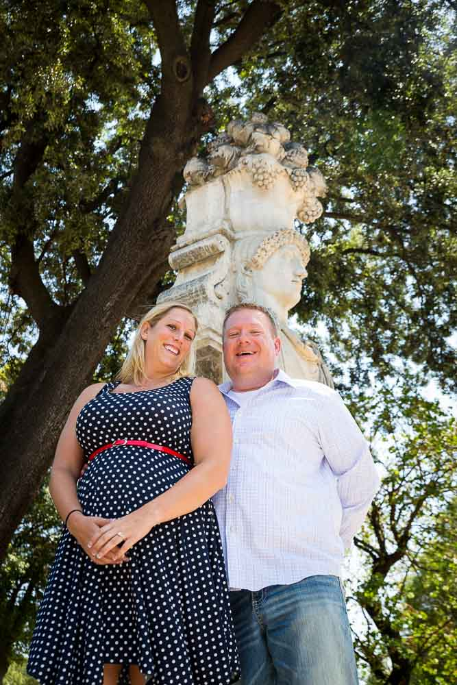 Couple standing underneath a statue in a park