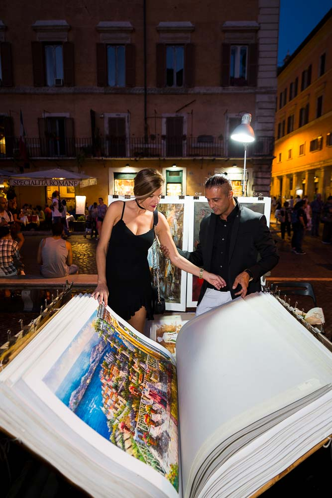 Flipping through poster paintings at the Piazza Navona at night during a couple photo shoot in Rome