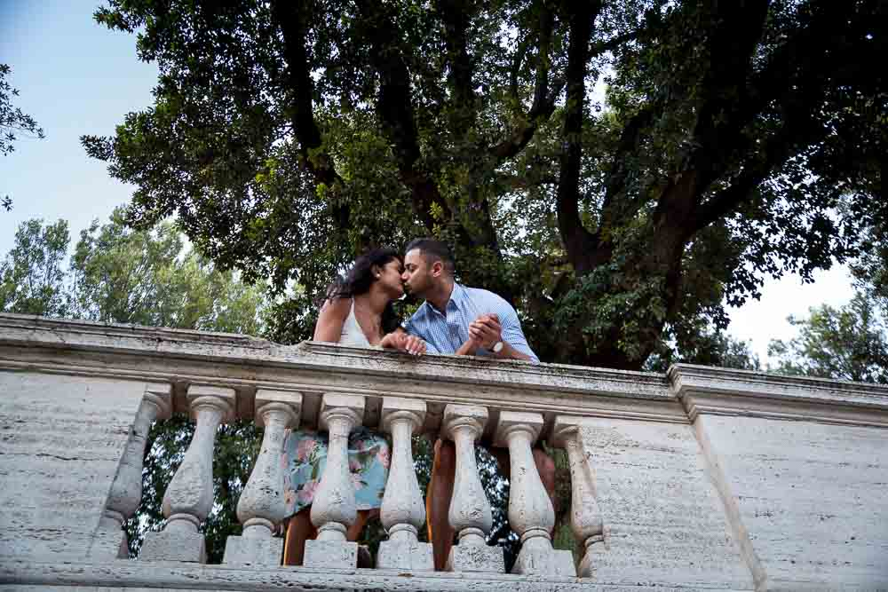 Couple in love kissing underneath a large tree in a park