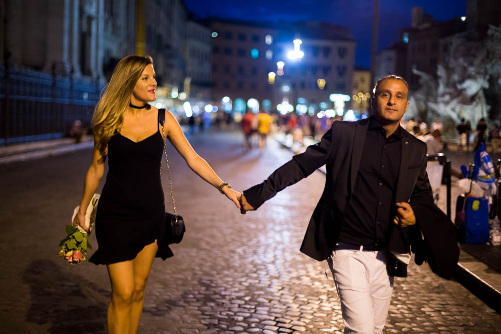Walking hand in hand in Navona square at night