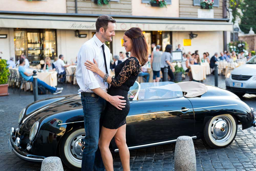 Just engaged couple before a vintage Porsche parked on a roman street