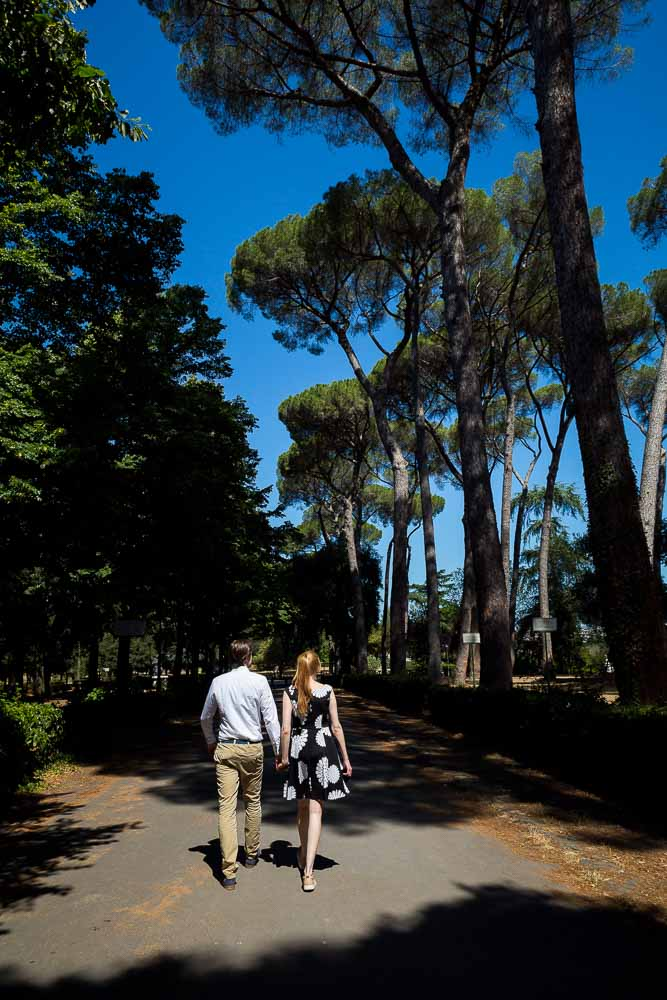 Walking hand in hand underneath Italian Mediterranean pine trees above