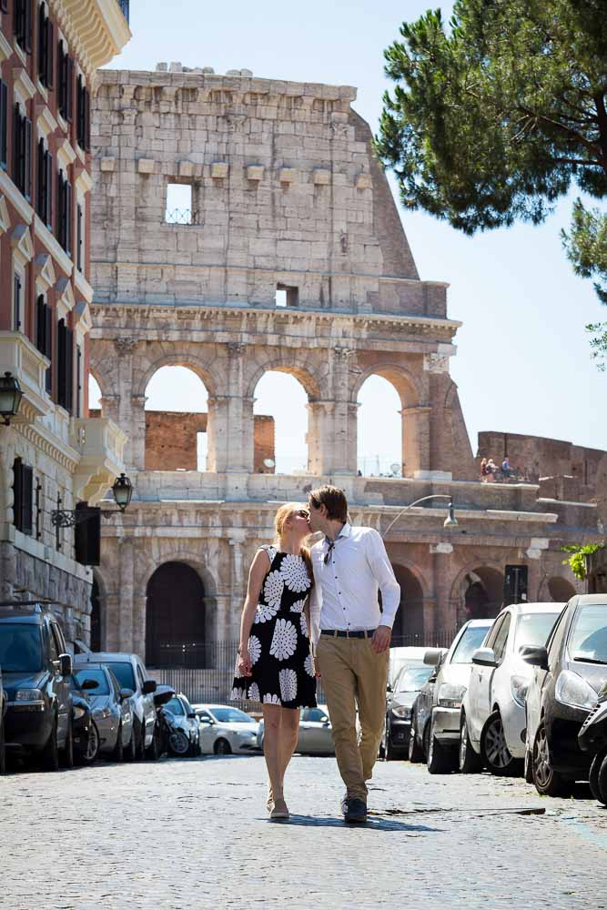 In love in Rome. Kissing in an alleyway with the Roman Colosseum in the background. Engagement photography.