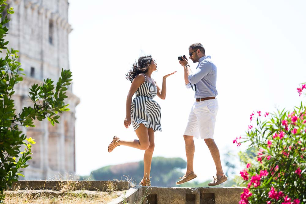 Engagement in Rome. Jumping up in the air and air blowing a kiss to a photographer taking pictures while jumping with the Colosseum in the background. Image by Andrea Matone