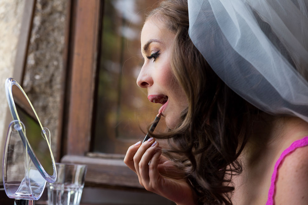 Bride putting on make up by the window