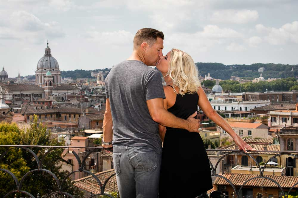 Couple kissing over the beautiful scenery of roman rooftops