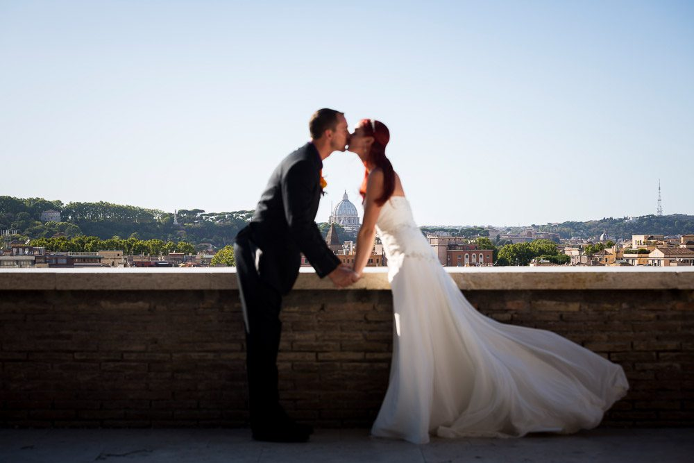 Kissing while framing Saint Peter's dome in the far distance. Rome, Italy