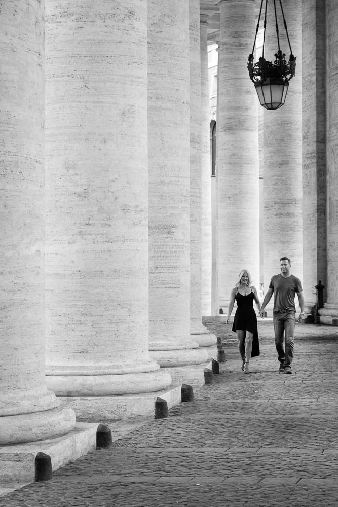Walking under massive columns in the Vatican. Black and white image