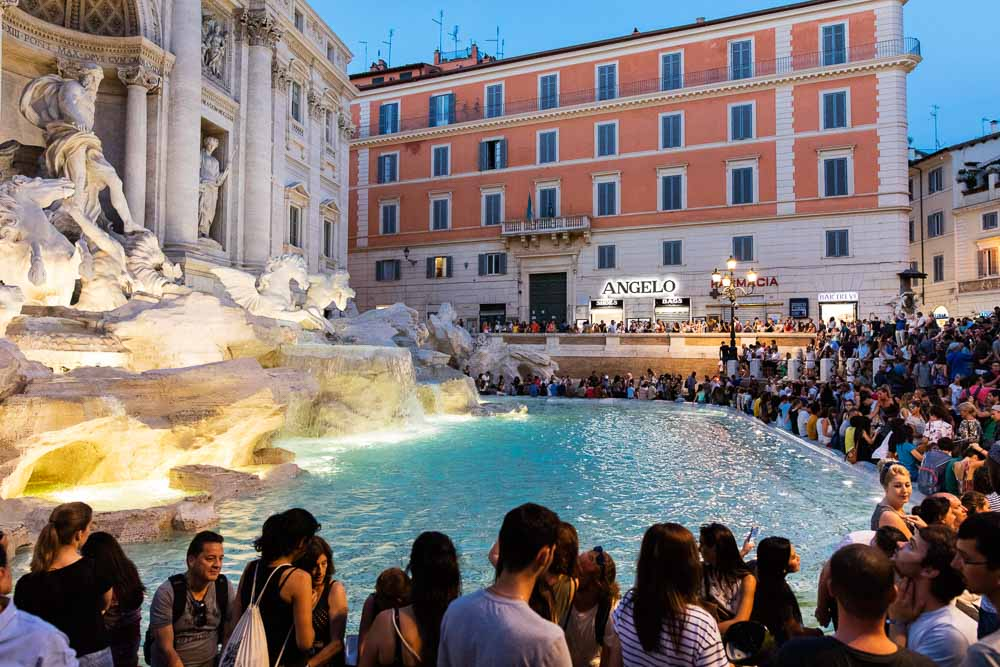 The crowd around fontana di trevi at night in the summer time
