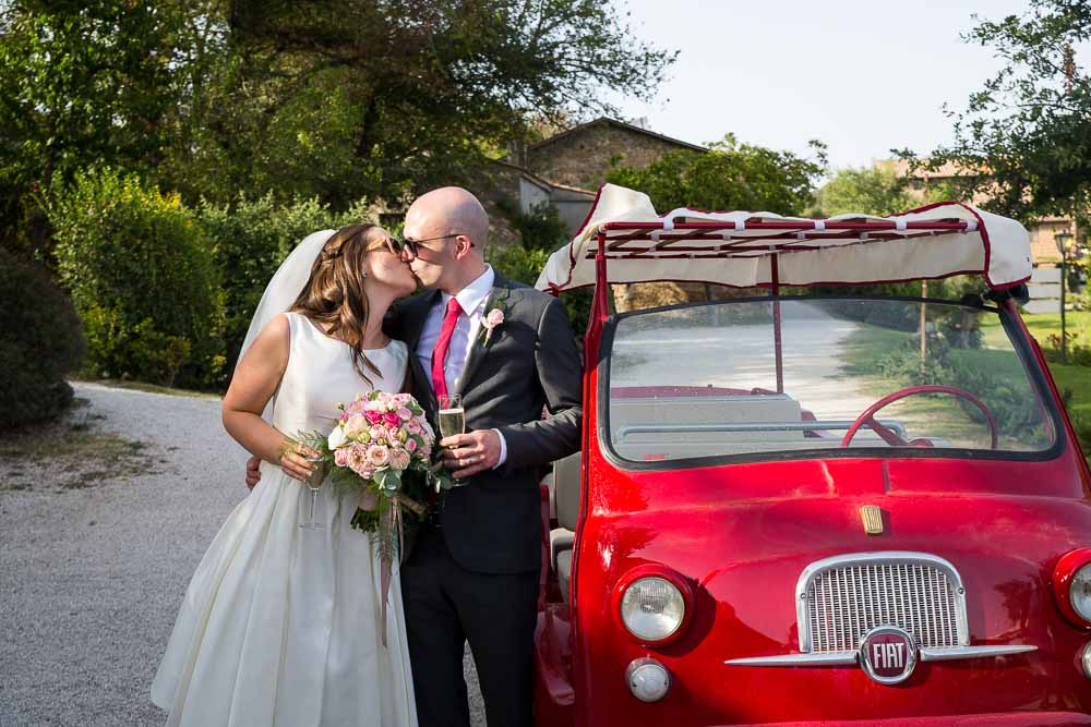 Bride & groom portrait by a bright red fiat vintage car