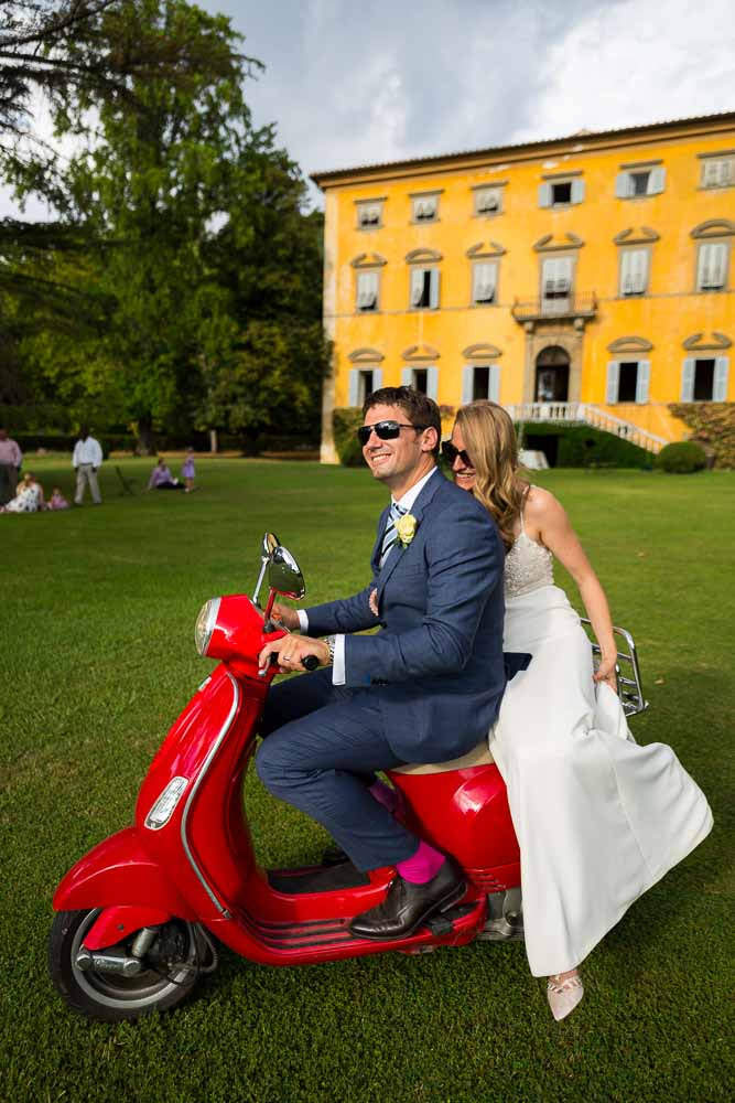 Married and taking a ride on a red Vespa in the Italian Tuscany countryside villa estate