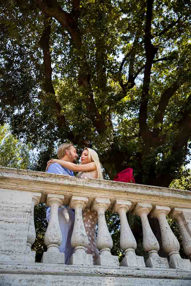 Kissing under illuminated park trees in Rome Italy