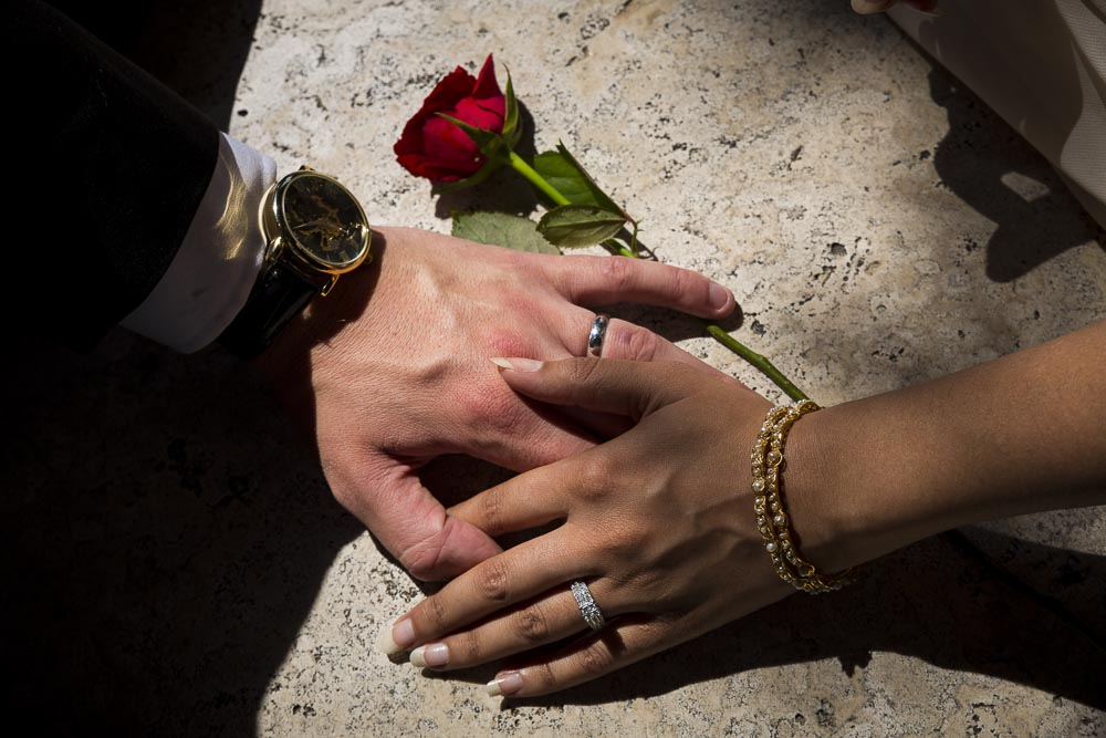 Macro image of a man and woman's hand with engagement rings and a red rose