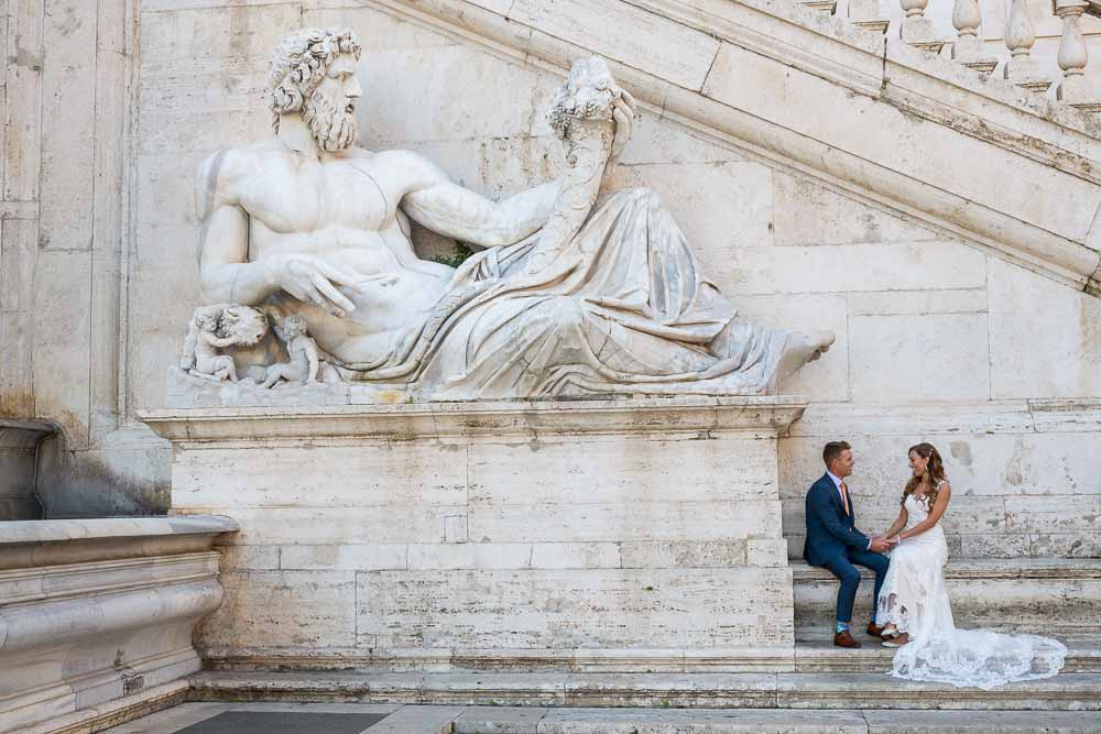 Bride and groom sitting next to a large roman marble statue