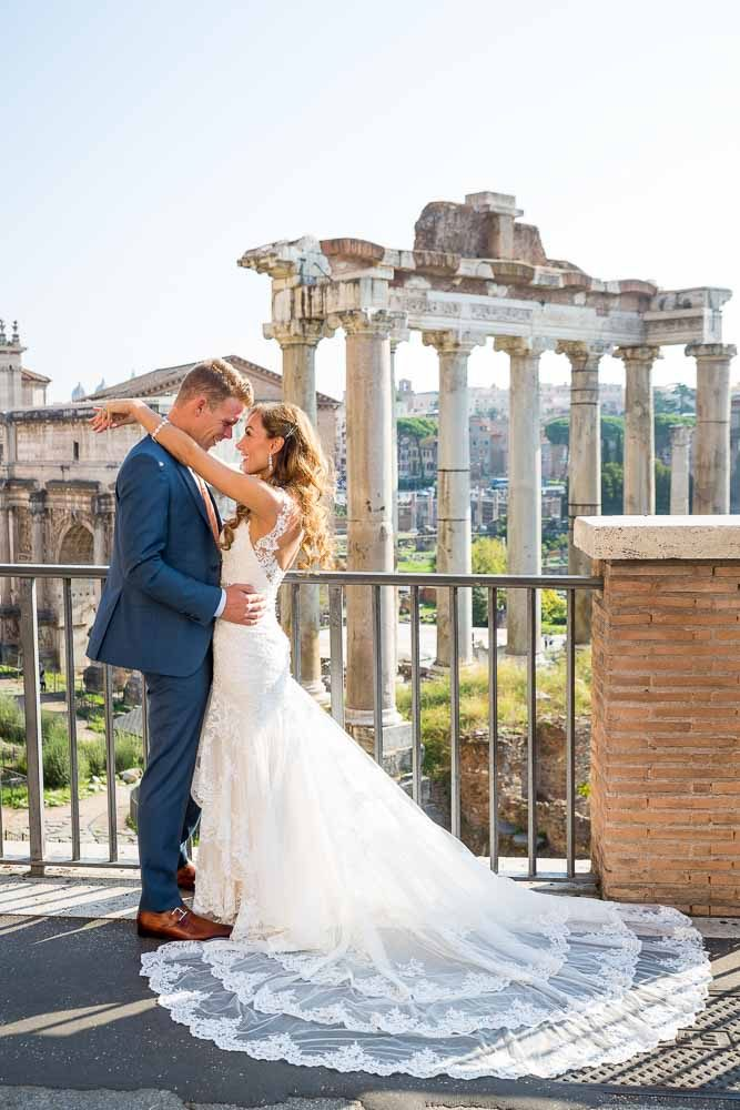 The groom and the bride posing in front of the ancient forum in Rome Italy