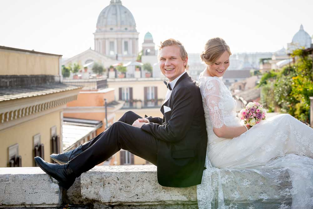 Groom and bride portrait before the Roman rooftops. In the center of Rome Italy