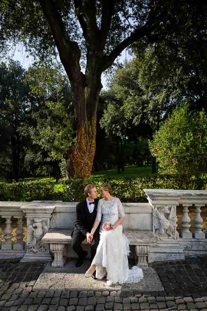 Portrait picture of a married couple sitting on a marble bench. Under Villa Borghese park trees.