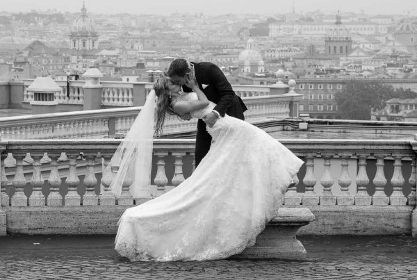 Grrom dipping the bride overlooking the roman rooftops