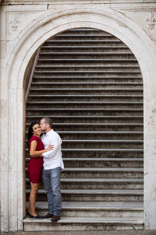 Coupe just engaged posing on a staircase underneath an arch