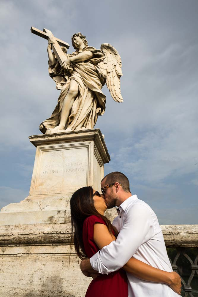 In love and kissing under an angel statue