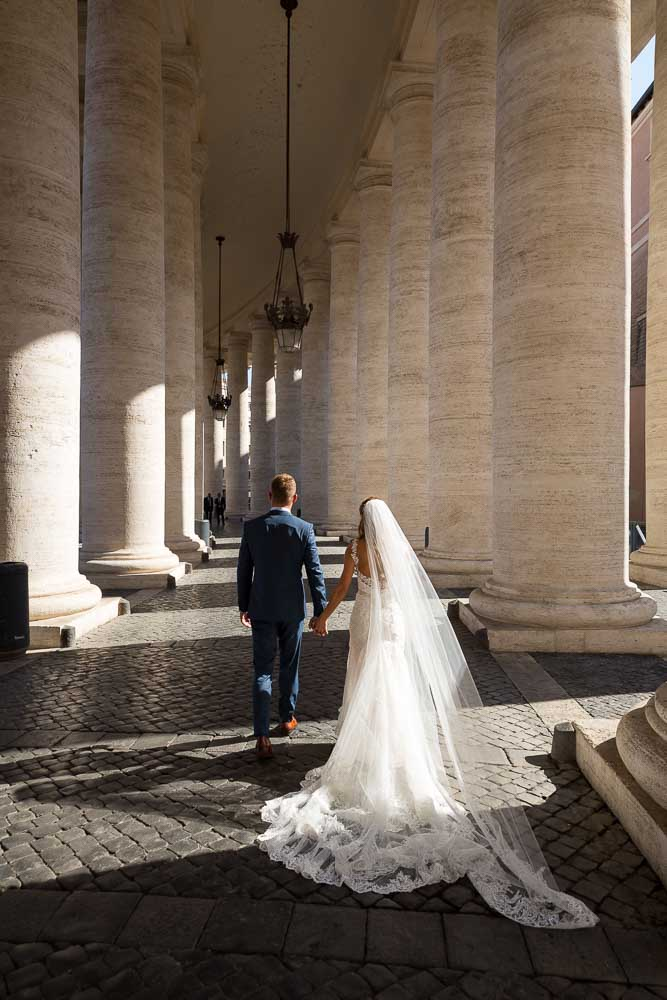 Walking underneath large marble columns at the Vatican
