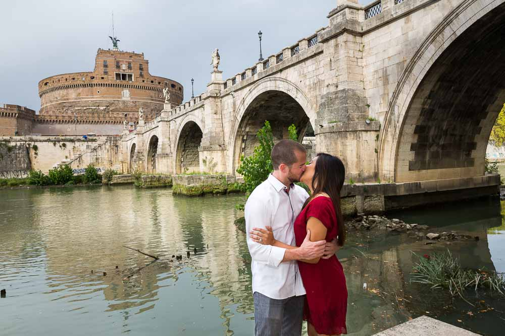 Together in Rome under the Castel Sant'Angelo bridge next to the Tiber river bank