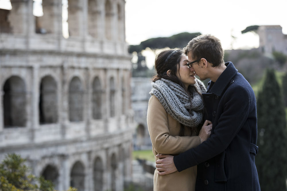 Romantic couple kissing in love at the Colosseum in Rome Italy