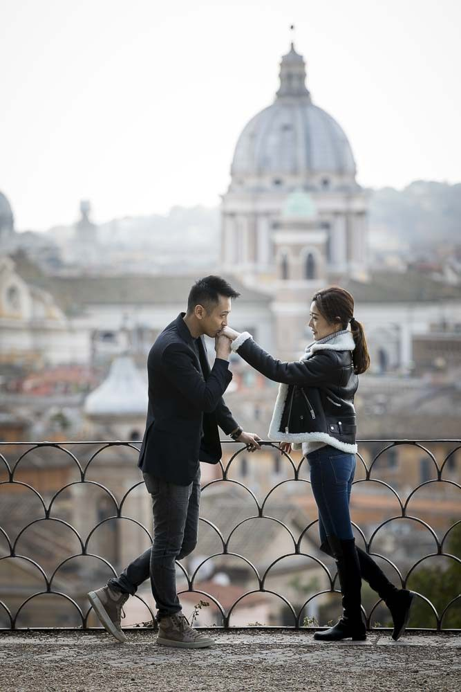 Chivalry moment of man kissing girlfriend's hand. Romance over the Roman rooftops during an engagement photography session in Rome