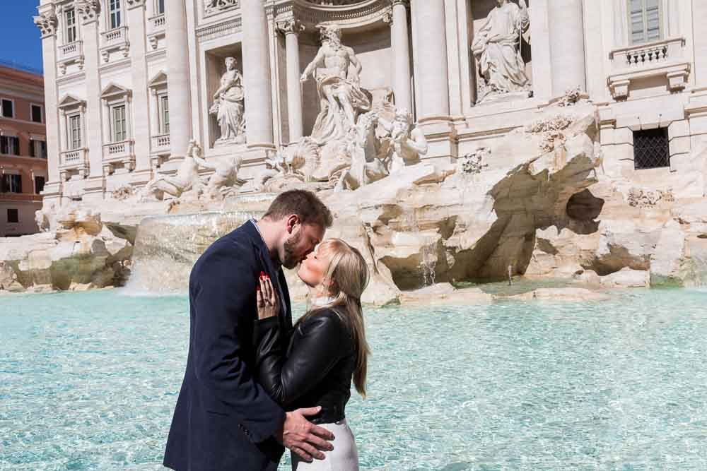 Kissing at the Trevi fountain during an engagement photo shoot in Rome