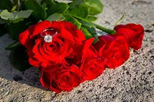 5 bright red roses with engagement ring