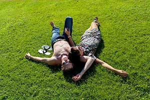Couple laying down on green grass