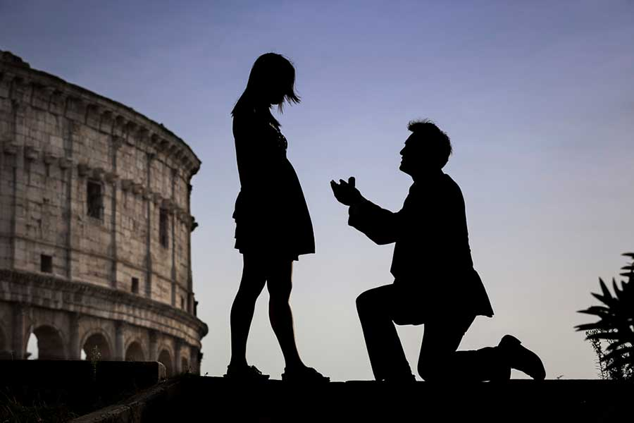 Surprise Wedding Proposal Photographer in Rome Italy. Image taken at the roman Coliseum at sunset.