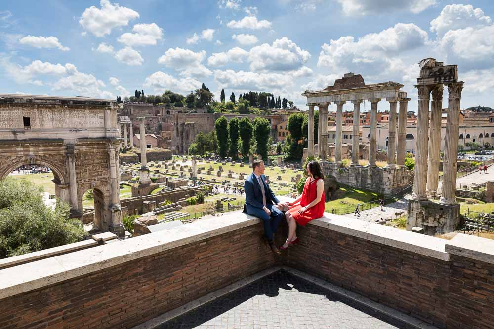 Honeymooners sitting down before the ancient roman site of the foro in Rome Italy