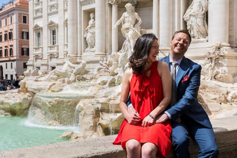 Newlyweds having fun at the Trevi fountain in the heart of Rome