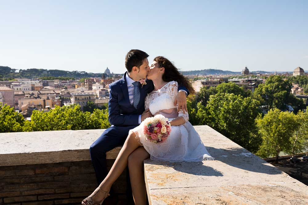 Bride and groom kissing over the roman rooftop view
