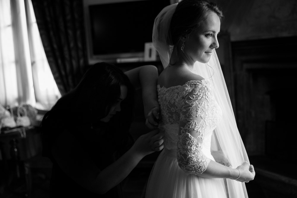 Black and white photography of the bride helped by the bridesmaid getting dress done