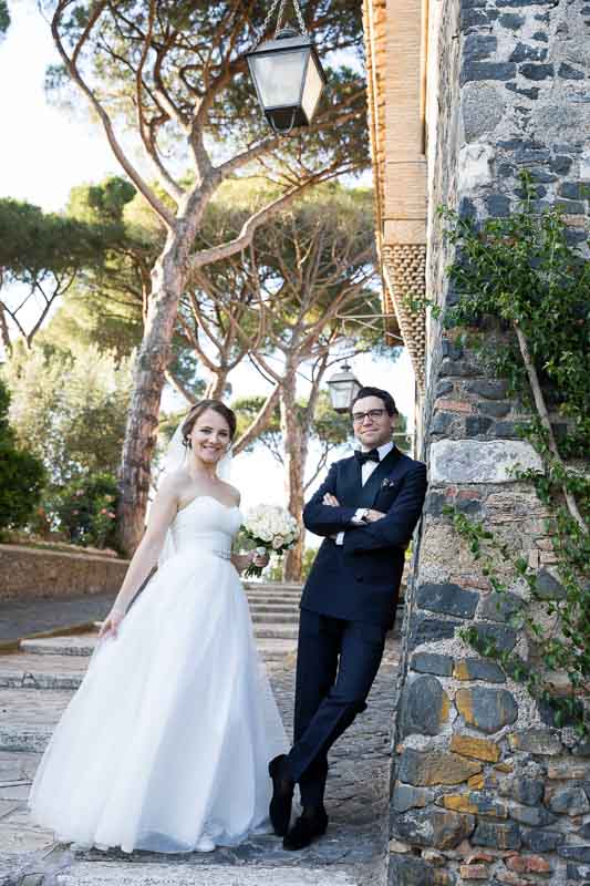 Evening wear bride and groom posing by the roman castle