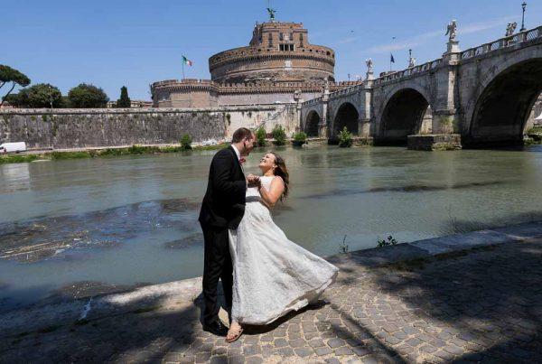 Wedding couple posing under Castel Sant Angelo bridge
