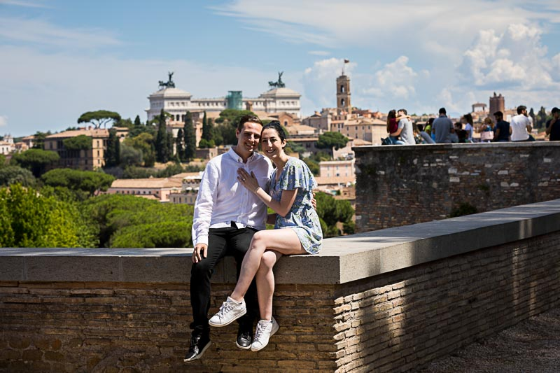 Couple sitting down before the scenic view of the roman skyline