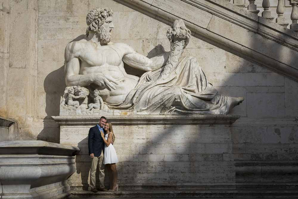 Engaged couple standing underneath a large marble statue