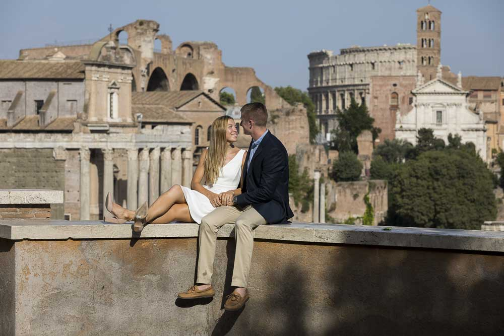 Sitting down portrait with the ancient city in the background. Engagement Photos in Ancient Rome