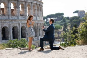 Fiancee proposing overlooking the roman Colosseum from a hillside overview