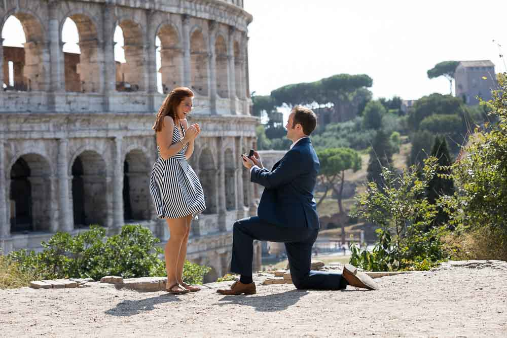 Fiancee proposing overlooking the roman Colosseum from a hillside overview. Engaged in Rome!